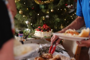 This photo shows a casual Australian Christmas lunch. A Barbecue lunch featuring charcoal grilled chicken, leg of ham, salads and dessert. In the foreground of the photo an elderly man helping himself to the buffet. The mighty pavlova is in focus with its cream, and berry topping. In the background you can see the Christmas tree with fairy lights and decorations.
