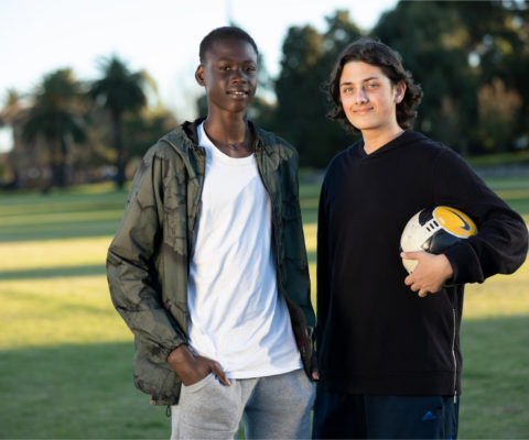 Two teenage boys, one holding a soccer ball under arm, standing in a field smiling.