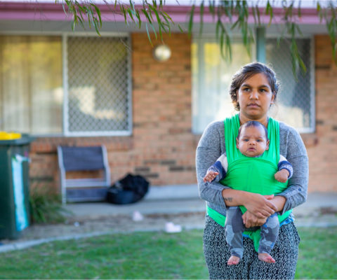 A mother holding a baby standing on the front lawn of a house.