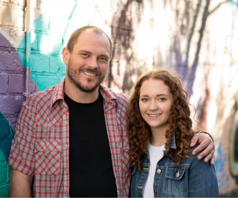 A father and daughter smiling at the camera in front of a painted brick wall