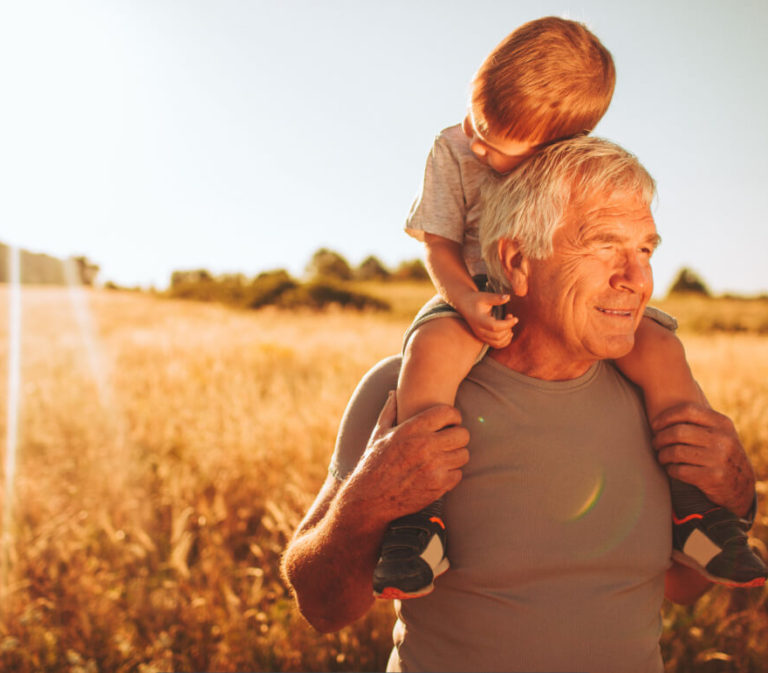 An older man with a child on his shoulders in a wheat field.