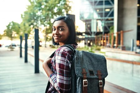 Teenage girl with backpack on smiling to the camera